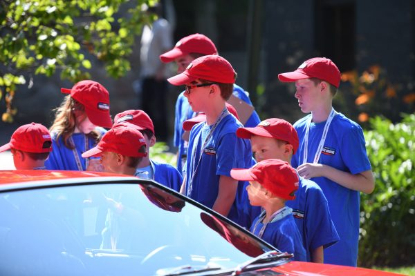 A group of kids in red hats and blue shirts judge a Panterra.