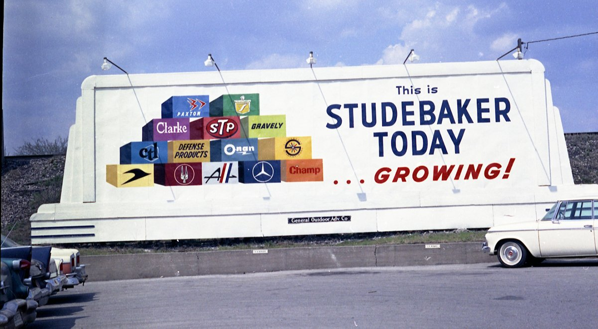 """A billboard advertises """"this is Studebaker Today...Growing! The logos of several Studebaker subsidiaries can be seen on the left side of the billboard."""