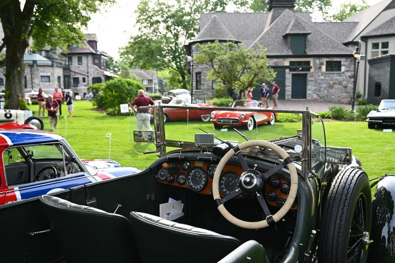 A 1936 Bentley 4 1/2 Litre LeMans RC Series sits in the foreground of the image. A Corvette and other American Sports Cars can be glimpsed in the background.